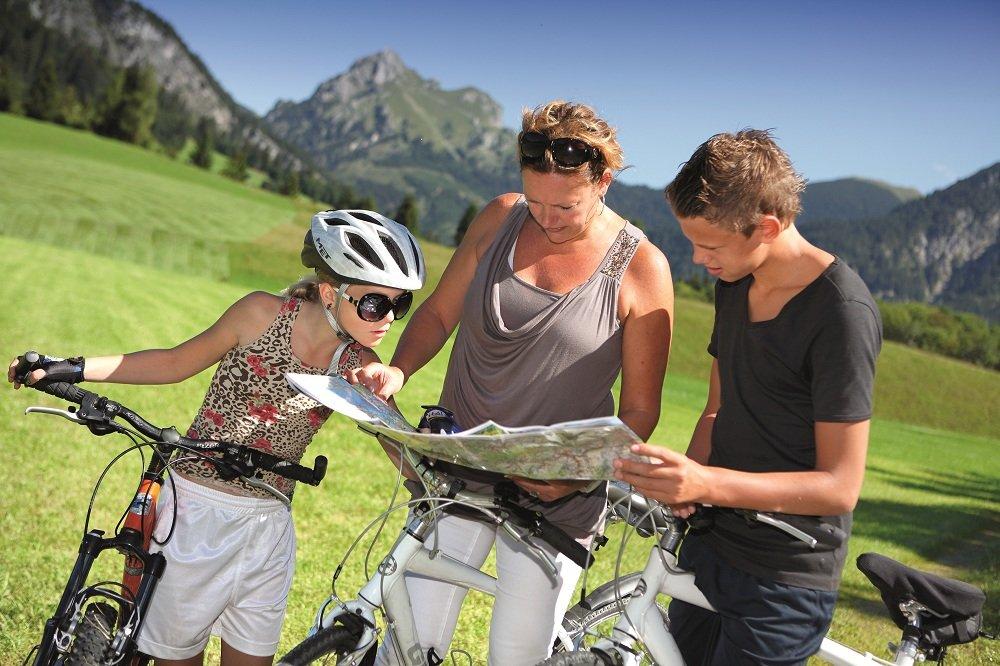 Moeder met 2 kinderen kaartlezen met op de achtergrond bergen