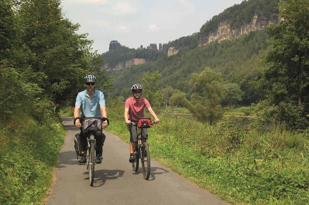 Fietspad met 2 fietsers met helmen en bergen er naast.