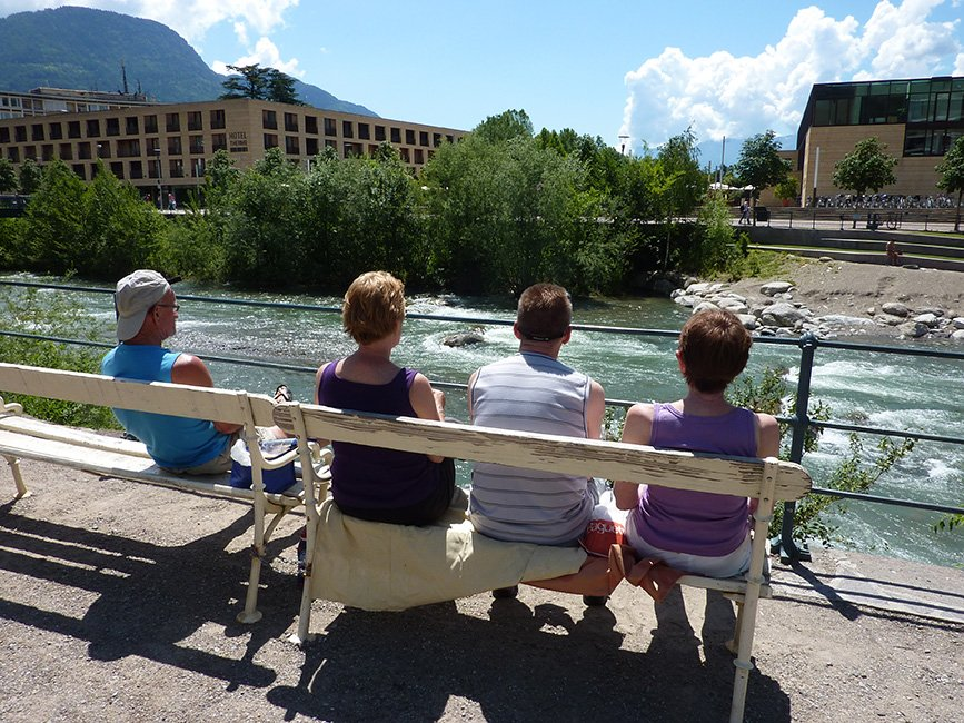 fietsers op bankje  bij rivier