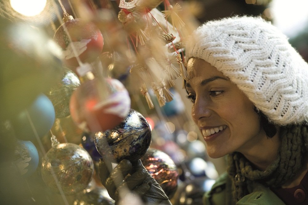 Vrouw bij kerstboom en kerstballen