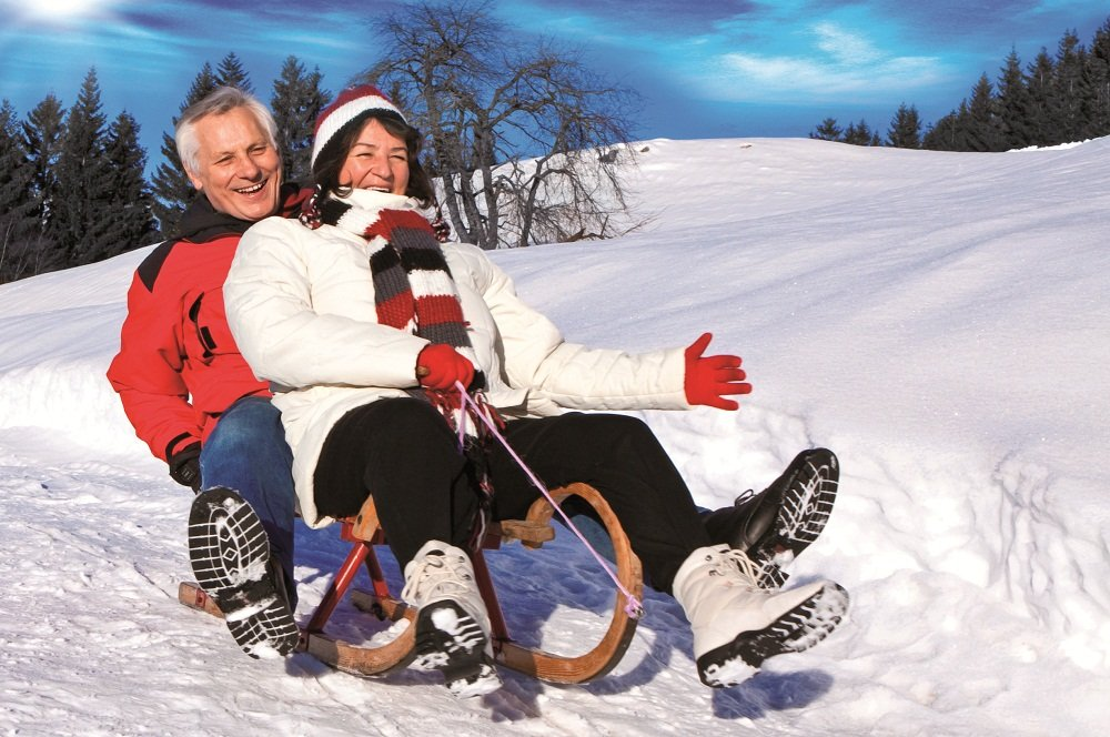 echtpaar op slee in sneeuw
