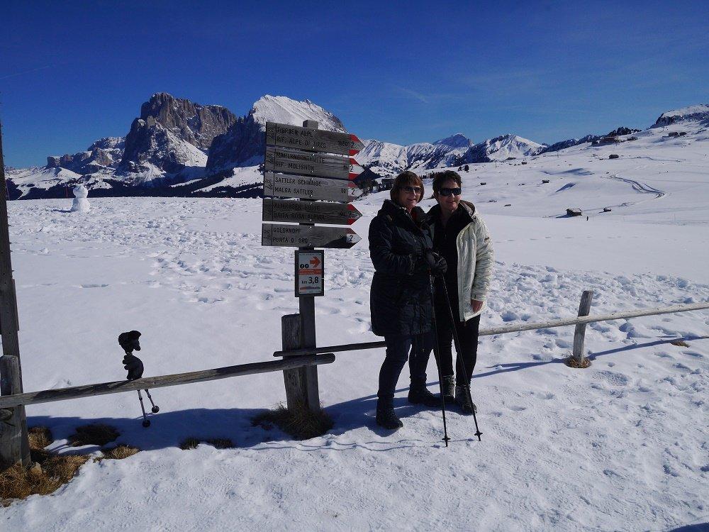 2 dames in de sneeuw bij bordje
